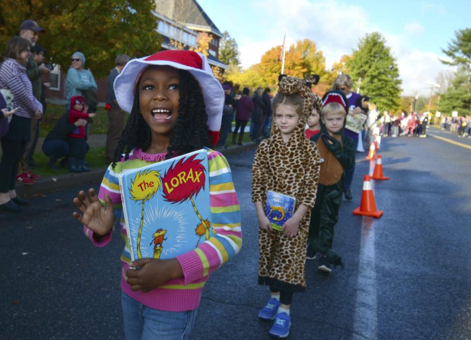"""Williamstown Elementary School children  participate in a character parade as part of their week-long """"Words are Wonderful"""" events which is in its 22nd year, Wednesday, Oct. 23, 2019 in Williamstown, Mass. Students, teachers and staff dressed as their favorite book character, or word, and marched with the book from which their character lives. The costume parade coincides with Halloween which is only a week away. (Gillian Jones/The Berkshire Eagle via AP)"""