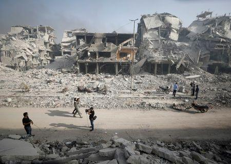 A Syrian army soldier walks past the rubble of damaged buildings in al-Hajar al-Aswad