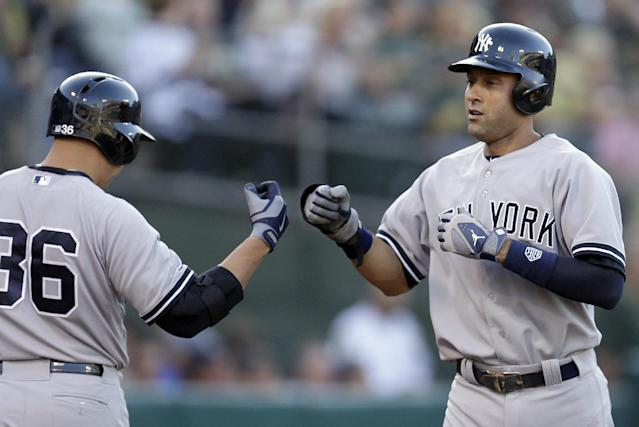 New York Yankees' Derek Jeter, right, is congratulated by teammate Carlos Beltran (36) after scoring against the Oakland Athletics in the first inning of a baseball game Friday, June 13, 2014, in Oakland, Calif. Jeter scored on a sacrifice fly by Mark Teixeira. (AP Photo/Ben Margot)