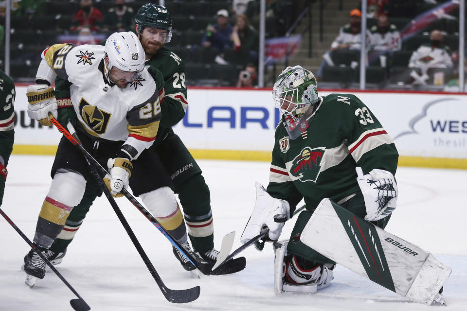 Minnesota Wild's goalie Cam Talbot (33) blocks the puck from the net against Vegas Golden Knights' William Carrier (28) during the second period in Game 3 of a first-round NHL hockey playoff series Thursday, May 20, 2021, in St. Paul, Minn. (AP Photo/Stacy Bengs)