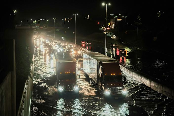 Vehicles cautiously drive through floodwaters on I-94 following a severe storm system that caused flash flooding on main roadways in Detroit.