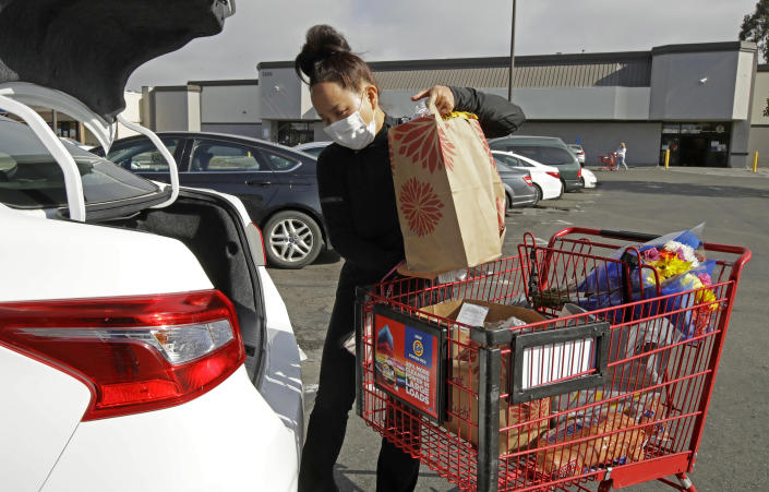 FILE - In this July 1, 2020 file photo, Instacart worker Saori Okawa loads groceries into her car for home delivery in San Leandro, Calif. A battle between the powerhouses of the so-called gig economy and big labor could become the most expensive ballot measure in California history. Voters are being asked to decide via Proposition 22 whether to create an exemption to a new state law aimed at providing wage and benefit protections to Uber, Lyft and other app-based drivers.Okawa, who drove 10 hours a day, six days a week for Uber for a year in San Francisco and now delivers food, said she's opposed to the ballot measure because she wants more protections for drivers, many of whom are immigrants like her. (AP Photo/Ben Margot, File)