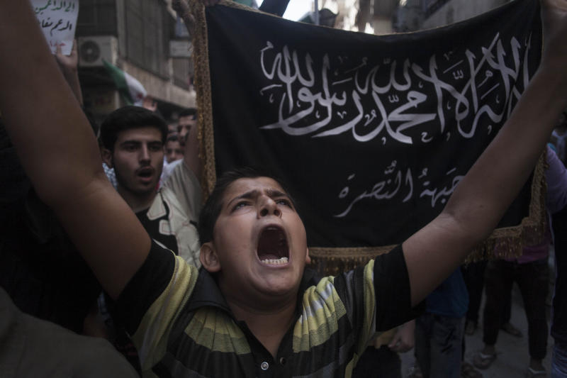 "FILE - In this Friday, Sept. 21, 2012 file photo, a Syrian boy shouts slogans against the regime in front of a flag of the armed Islamic opposition group, the Nusra front, during a demonstration in the Bustan al-Qasr neighborhood of Aleppo, Syria. Activists said on Saturday, July 13, 2013 that Syrian rebels and fighters from an al-Qaida-linked group have turned their guns on each other and are fighting for control of a key checkpoint in the northern city of Aleppo. The checkpoint is the only gateway between rebel-held eastern districts and the city's western areas, controlled by President Bashar Assad's troops. Arabic on banner in background contains words from the Quran and reads, ""There is not God but Allah, and Muhammad is his messenger, the Nusra front"" (AP Photo/ Manu Brabo, File)"
