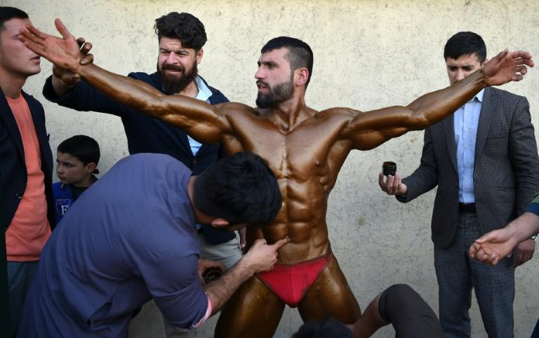 Bodybuilder Hares Mohammadi, 25, being covered in fake tan during a contest in Kabul