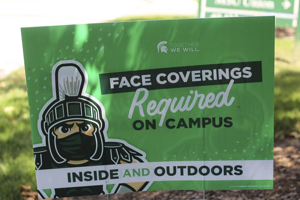 A sign outside the Michigan State University Student Union building alerts students to MSU's face covering rule on Friday, Aug. 21, 2020. Students at Michigan universities are receiving emails from their schools welcoming them back for the fall, but a cloud of concern is hovering because of the coronavirus pandemic. To go online or to come in person has been the debate, but since Michigan State University announced Tuesday it will go online for the next semester, the debate is reaching a fever pitch. (AP Photo/Anna Nichols)