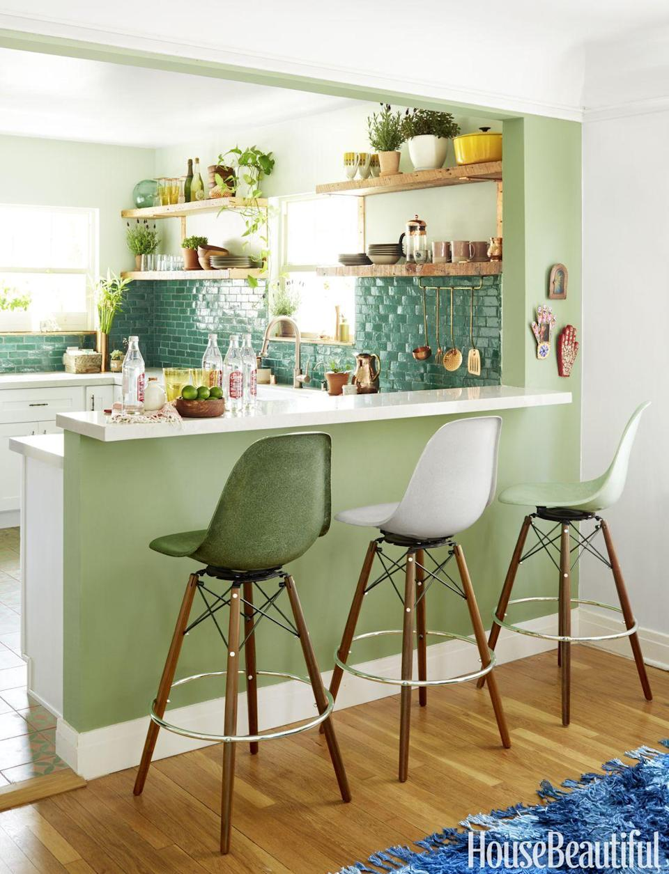 "<p>A pale green blends seamlessly between the kitchen and dining area of this <a href=""https://www.housebeautiful.com/design-inspiration/house-tours/g3610/justina-blakeney-jungalow-tour/"" rel=""nofollow noopener"" target=""_blank"" data-ylk=""slk:&quot;jungalow,&quot;"" class=""link rapid-noclick-resp"">""jungalow,""</a> by Justina Blakeney, especially when paired with the Moroccan clay tile backsplash and ombre dining bar stools in the living room. </p>"