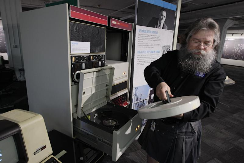 In this photo taken Oct. 30, 2012, Ian King, senior vintage systems engineer at the Living Computer Museum in Seattle, loads a large disk drive that holds 5mb of data into a working DEC 11/70 minicomputer from 1975. The machine is part of the collection of running computers at Paul Allen's newly opened Living Computer Museum. For tourists with an interest in Seattle's role as a high-tech hub, there hasn't been much here to see, other than driving over to Microsoft headquarters in suburban Redmond to take pictures of a bunch of boring buildings. But Microsoft co-founder Paul Allen has just opened the Living Computer Museum, with displays of old machines _ all in working order _ along with a geeky wish list of items he'd like to add, just in case anybody out there has an old tape drive or super-computer sitting around. (AP Photo/Ted S. Warren)