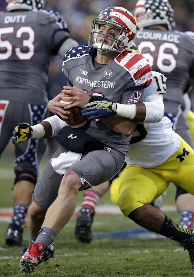 Michigan linebacker James Ross III (15) sacks Northwestern quarterback Trevor Siemian during the first half of an NCAA college football game in Evanston, Ill., Saturday, Nov. 16, 2013. (AP Photo/Nam Y. Huh)