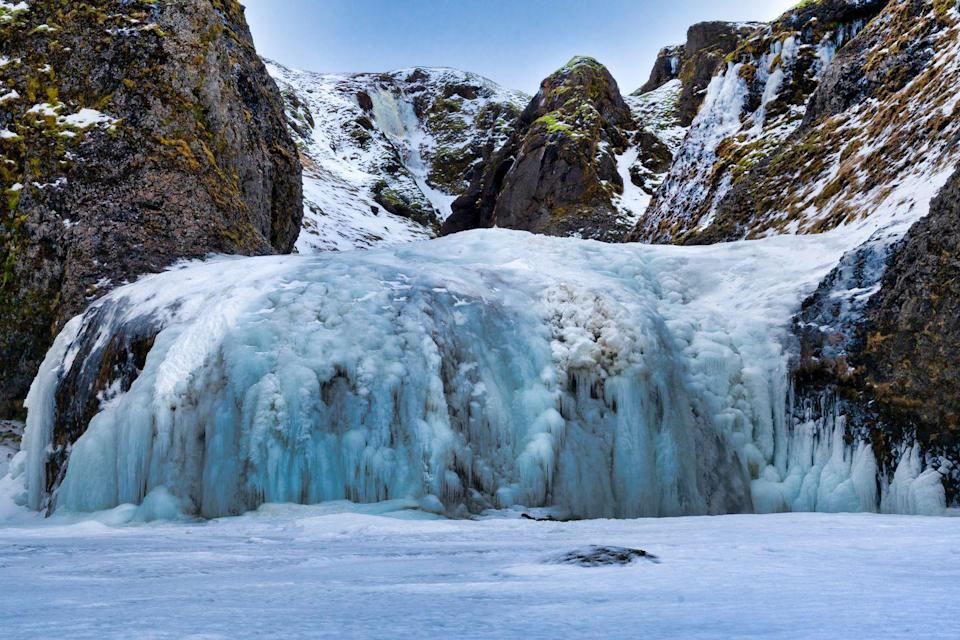 <p>This expansive waterfall in Iceland covers the rock formation and looks like a big frozen bubble. </p>