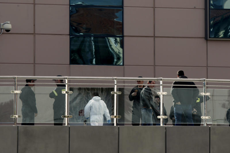 Security officers stand outside a mall following a blast in Athens, Sunday, Jan. 20 2013. A bomb exploded Sunday at a shopping mall in Athens, slightly wounding two security guards, police said. (AP Photo/Kostas Tsironis)