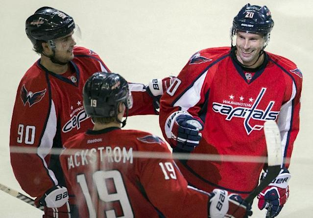 Washington Capitals right wing Troy Brouwer, right, is congratulated by center Marcus Johansson, left, and center Nicklas Backstrom after scoring a goal during the third period of an NHL hockey game on Sunday, March 16, 2014, in Washington. The Capitals won 4-2. (AP Photo/ Evan Vucci)