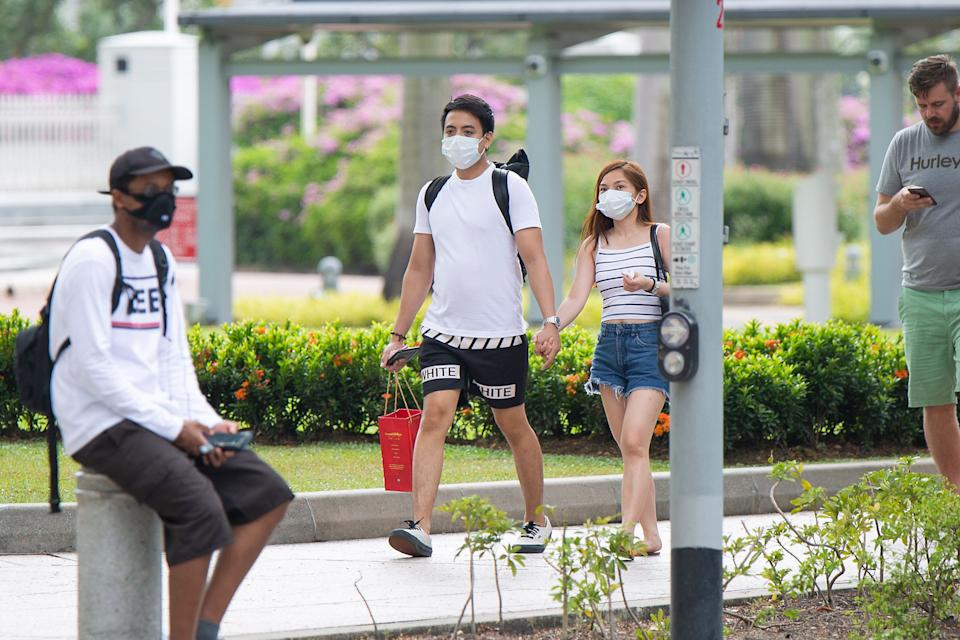 A couple wearing face masks seen walking outside Parliament House on Monday (27 January). (PHOTO: Dhany Osman / Yahoo News Singapore)