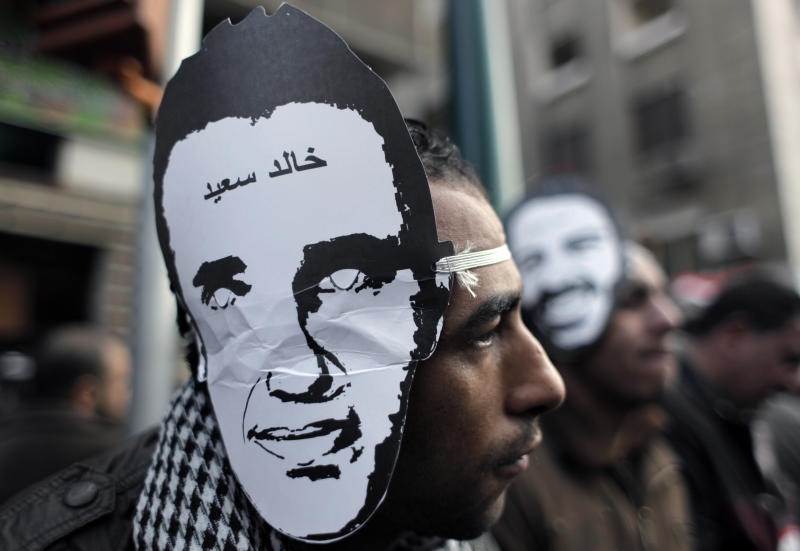 "FILE - In this Monday, Jan. 23, 2012 file photo, Egyptian protesters, one wearing a mask depicting slain Egyptian activist Khaled Saed, with Arabic that reads ""Khaled Saed,"" next to riot police outside the Egyptian People's Assembly building during parliament's opening session in Cairo, Egypt. An extreme case of police brutality that killed Khaled Saed was a key inspiration for the uprising. The Facebook group that called the early protests was called ""We are all Khaled Saed."" (AP Photo/Nasser Nasser, File)"