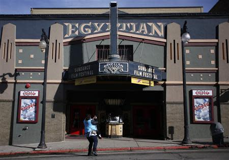 A woman uses a mobile phone to take pictures of the Egyptian Theater before the opening day of the Sundance Film Festival in Park City, Utah, January 15, 2014. REUTERS/Jim Urquhart