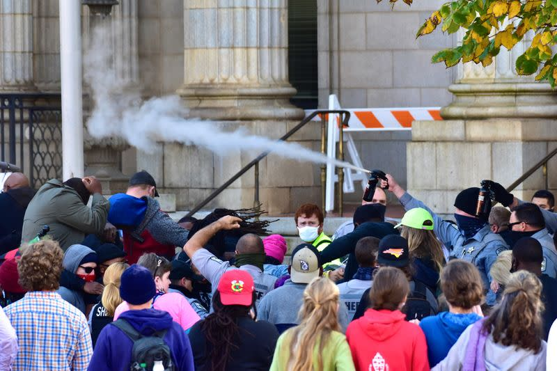 Law enforcement officers spray protesters shortly after a moment of silence during a Get Out The Vote march in Graham