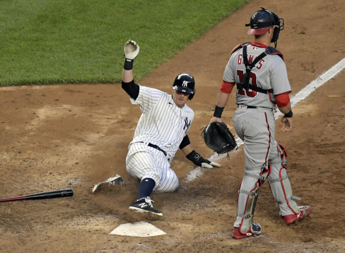 New York Yankees' DJ LeMahieu scores the winning run on an infield single by Gleyber Torres as Washington Nationals catcher Yan Gomes (10) walks away in the 11th inning of a baseball game, Saturday, May 8, 2021, at Yankee Stadium in New York. The Yankees won 4-3. (AP Photo/Bill Kostroun)
