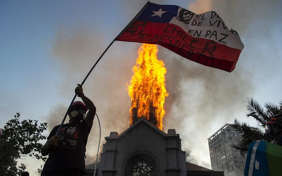 A demonstrator flutters a Chilean flag outside the burning church of Asuncion - AFP