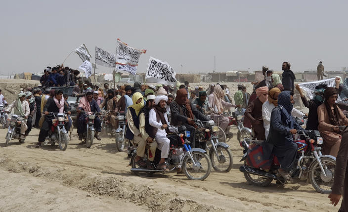 FILE - In this July 14, 2021 file photo, supporters of the Taliban carry their signature white flags after the Taliban said they seized the Afghan border town of Spin Boldaka across from the town of Chaman, Pakistan. In an interview with The Associated Press Thursday, July 22, 2021, Suhail Shaheen, Afghan Taliban spokesman and a member of the Taliban negotiation team, said the insurgent movement does not want to monopolize power, but there won't be peace until there is a new, negotiated government in Kabul and Afghan President Ashraf Ghani is removed. Shaheen said women will be allowed to work, go to school, and participate in politics but will have to wear the hijab, or headscarf. (AP Photo/Tariq Achkzai, File)