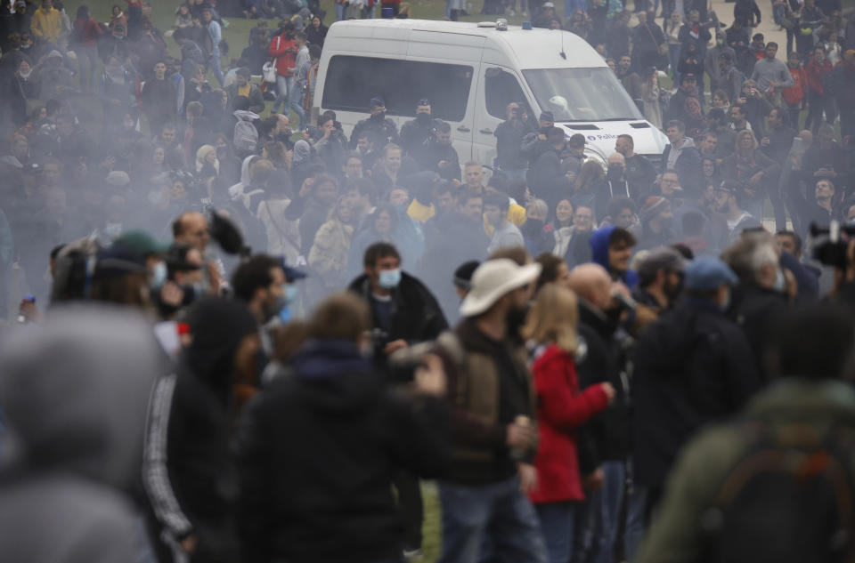 "Police patrol in a van as people gather at the Bois de la Cambre park for a party called ""La Boum 2"" in Brussels, Saturday, May 1, 2021. Police put on extra patrols Saturday to monitor the gathering which is being held in defiance of Belgium's current COVID-19 regulations. (AP Photo/Olivier Matthys)"