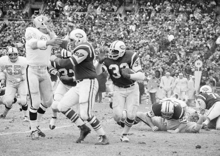 File-This Dec. 6, 1970 file photo shows New York Jets running back Emerson Boozer (32) goes for a three-yard gain in the second quarter at New York's Shea Stadium as Jets' tight end Pete Lammons fends off Oakland Raiders' linebacker Gus Otto (34). Lammons, a tight end on the New York Jets' Super Bowl-winning team in 1969, has died in a boating accident. He was 77. Major League Fishing announced in a statement Friday, April 30, 2021, that Lammons was participating in a fishing event on the Sam Rayburn Reservoir in Texas on Thursday morning when he slipped while boarding a boat, fell into the water, and drowned. (AP Photo/Harry Harris, File)