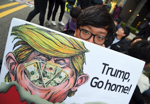 <p>A South Korean protestors displays a placard showing a caricature of President Donald Trump during an anti-Trump rally in Seoul on Nov. 4, 2017, ahead of Trump's visit to South Korea. (Photo: Jung Yeon-Je/AFP/Getty Images) </p>