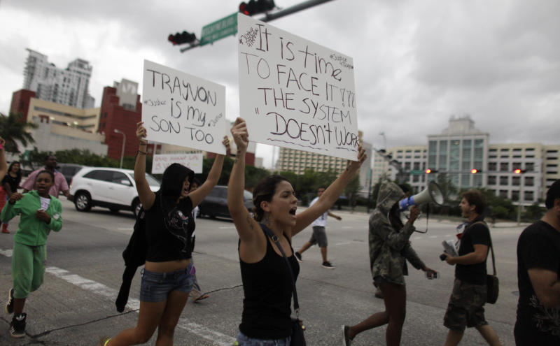 Demonstrators hold signs as they march during a vigil for Trayvon Martin on Sunday, July 14, 2013, in Miami, Fla. Demonstrators upset with the verdict protested mostly peacefully in Florida, Milwaukee, Washington, Atlanta and other cities overnight and into the early morning.(AP Photo/Javier Galeano)