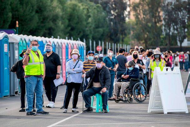 PHOTO: People wait in line in a Disneyland parking lot to receive Covid-19 vaccines on the opening day of the Disneyland Covid-19 vaccination 'super Point-of-Dispensing' (POD) site, January 13, 2021, in Anaheim, California. (Valerie Macon/AFP via Getty Images)