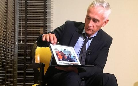 Jorge Ramos shows a video he says his crew shot showing Venezuelan youth picking food scraps out of the back of a garbage truck in Caracas. Mr Ramos claims it was this footage which prompted the team's detention - Credit: STF