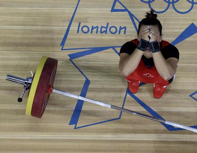 Christine Girard of Canada reacts while competing in the women's 63-kg weightlifting competition at the 2012 Summer Olympics, Tuesday, July 31, 2012, in London. (AP Photo/Ng Han Guan)
