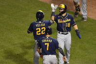 Milwaukee Brewers' Christian Yelich (22) celebrates with teammates Keston Hiura (18) and Eric Sogard (7) after hitting a three-run home run during the sixth inning of a baseball game against the Chicago Cubs, Friday, Aug. 14, 2020, in Chicago. (AP Photo/Jeff Haynes)