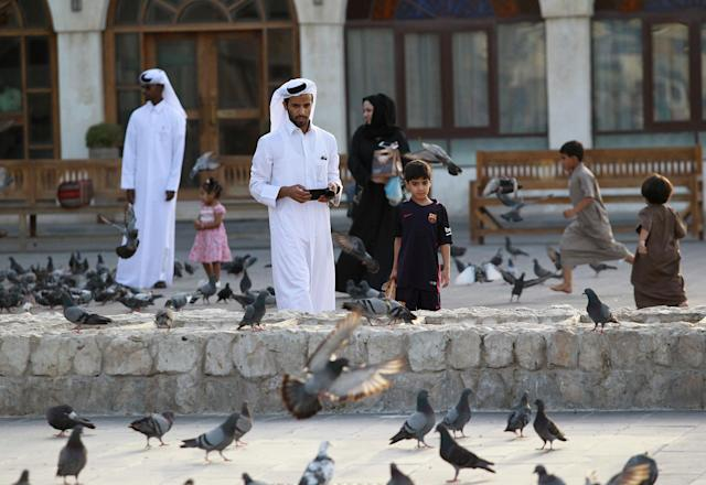 <p>People look at pigeons at Souq Waqif market in Doha, Qatar, June 6, 2017. (Photo: Naseem Zeitoon/Reuters) </p>