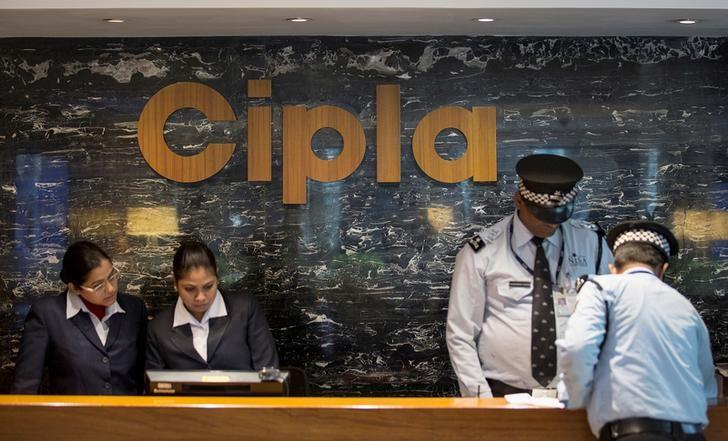Employees and security staff work at the reception area of Cipla at its headquarters in Mumbai