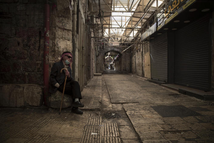 A Palestinian man sits in front of closed shops during a general strike, in the West Bank city of Nablus, Tuesday, May 18, 2021. Palestinian leaders are calling for a general strike in Gaza, the West Bank and within Israel to protest against Israel's air strikes on Gaza and the violent confrontations between Israeli security forces and Palestinians in Jerusalem. (AP Photo/Majdi Mohammed)