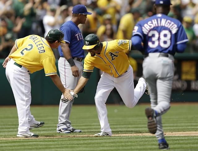 Oakland Athletics' Coco Crisp, center, is congratulated by third base coach Mike Gallego (2) after Crisp hit a two run home run off Texas Rangers' Derek Holland in the fifth inning of a baseball game, Monday, Sept. 2, 2013, in Oakland, Calif. At right, Rangers manager Ron Washington runs onto the field to talk with umpires. (AP Photo/Ben Margot)