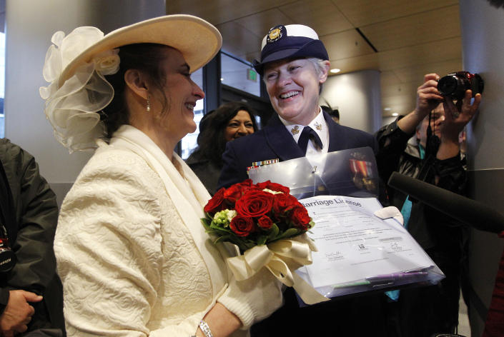 Retired U.S. Coast Guard Petty Officer 1st Class Nancy Monahan, right, wears her dress uniform as she holds her marriage license and stands with her soon-to-be bride Deb Needham as they wait at Seattle City Hall, Sunday, Dec. 9, 2012, in Seattle. The couple is from Renton, Wash. Gov. Chris Gregoire signed a voter-approved law legalizing gay marriage Wednesday, Dec. 5 and weddings for gay and lesbian couples began in Washingtons state on Sunday, following the three-day waiting period after marriage licenses were issued earlier in the week. (AP Photo/Elaine Thompson)