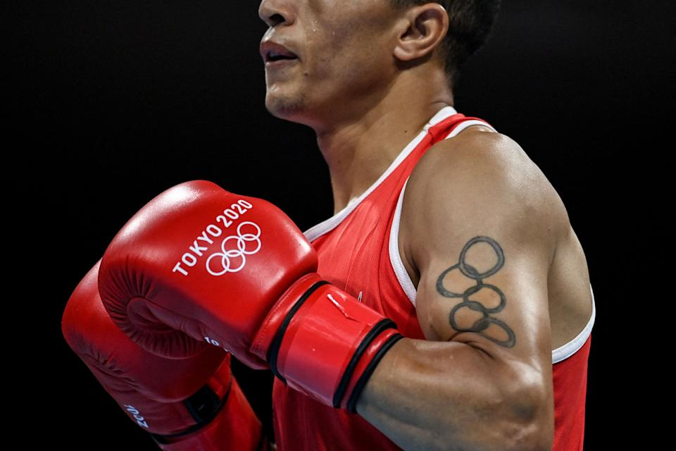 <p>Detail of the tattoo of Morocco's Abdelhaq Nadir depicting Olympic rings as he fights Mauritius' Louis Richarno Colin during their men's light (57-63kg) preliminaries boxing match during the Tokyo 2020 Olympic Games at the Kokugikan Arena in Tokyo on July 25, 2021. (Photo by Luis ROBAYO / POOL / AFP) (Photo by LUIS ROBAYO/POOL/AFP via Getty Images)</p>