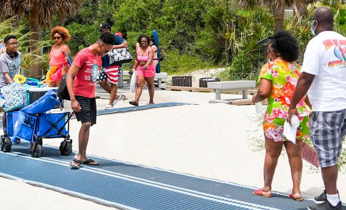 Few beach goers wore face coverings when making their way on and off Hilton Head Island's beach on Saturday, June 27, 2020 on the narrow pathway near Coligny Beach Park.