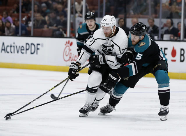 Anaheim Ducks defenseman Korbinian Holzer, right, of Germany, poke checks the puck away from Los Angeles Kings center Jeff Carter, center, during the first period of an NHL hockey game in Anaheim, Calif., Sunday, March 10, 2019. (AP Photo/Alex Gallardo)