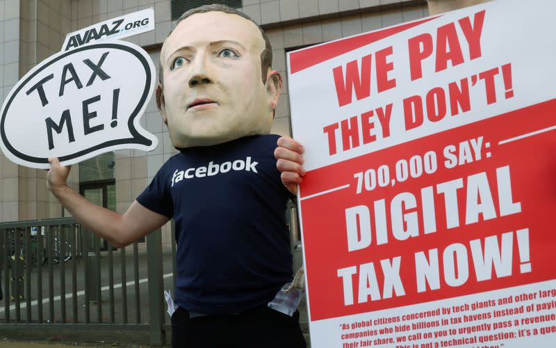 FILE PHOTO: An activist wearing a mask depicting Facebook's CEO Mark Zuckerberg demonstrates during the European Union finance ministers meeting, outside the EU headquarters in Brussels
