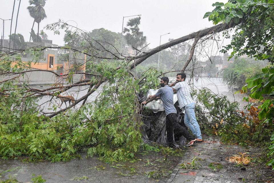 Locals clear a fallen tree from a road following the landfall process of Cyclone Tauktae, in Surat, Gujarat, on Tuesday.