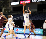 This photo provided by DePaul Athletics shows DePaul's Dee Bekelja (23) shooting during a women's NCAA college basketball game against Texas A&M on Saturday, Nov. 28, 2020, in Chicago. It's a common sight to see players and coaches wear masks on the sideline so far this season during college basketball games to help prevent the spread of the coronavirus. The DePaul and Creighton women's basketball teams are among a few squads that have taken it a step further with their players wearing the masks while they are on the court playing. (Steve Woltmann/DePaul Athletics via AP)
