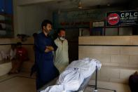 Family members stand beside a body of a relative, who was killed in a plane crash, in Karachi