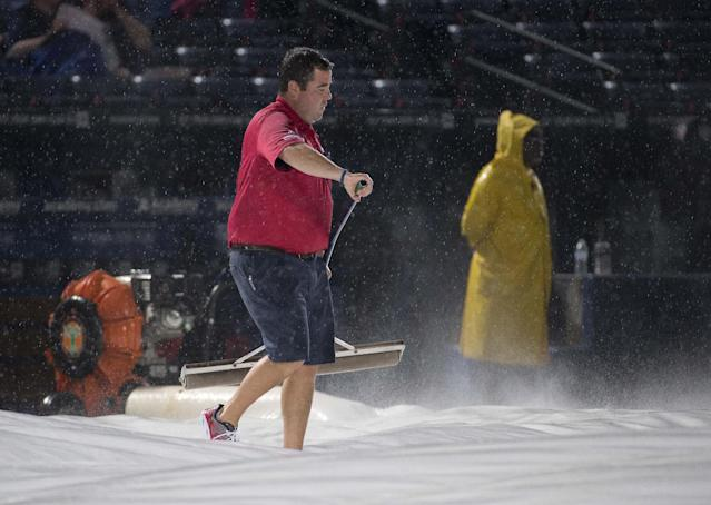 A member of the Atlanta Braves grounds crew clears water from the tarp before a baseball game between the Atlanta Braves and the Washington Nationals on Saturday, Aug. 9, 2014, in Atlanta. (AP Photo/John Bazemore)