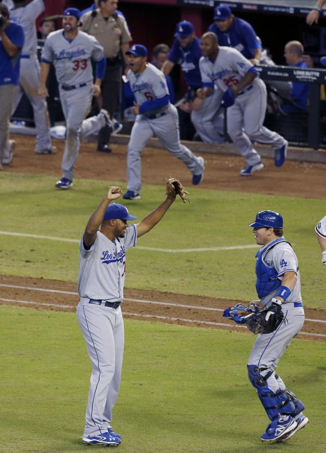 Los Angeles Dodgers' Kenley Jansen, left, and A.J. Ellis, right, celebrate their win to capture the Western Division National League Championship after a baseball game against the Arizona Diamondbacks, Thursday, Sept. 19, 2013, in Phoenix. The Dodgers won 7-6. (AP Photo/Ross D. Franklin)