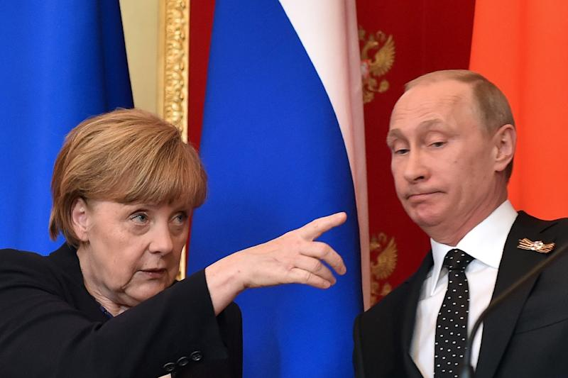 German Chancellor Angela Merkel (L) gestures as Russian President Vladimir Putin looks on during a joint press conference at the Kremlin in Moscow on May 10, 2015