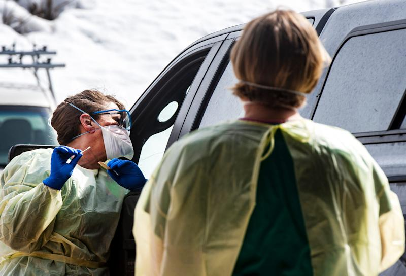 Infection Control's Amy Carter, left, and respiratory therapist Kim Thompson perform a real-time test for coronavirus on patients with appointments in Colorado outside the Aspen Volunteer Fire Department's Aspen Village Location on March 12, 2020. (Kelsey Brunner/The Aspen Times via AP)