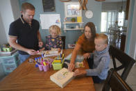 Brad and Stefanie Plothow home school their children Cameron, 9, in the 3rd grade, and Ainsley, 5, in kindergarten, Friday, Aug. 20, 2021, in Lehi, Utah. A group of Utah parents is suing the state over a law that bans school districts from approving mask mandates. It's the latest U.S. legal challenge over rules for face coverings in the classroom. (AP Photo/Rick Bowmer)