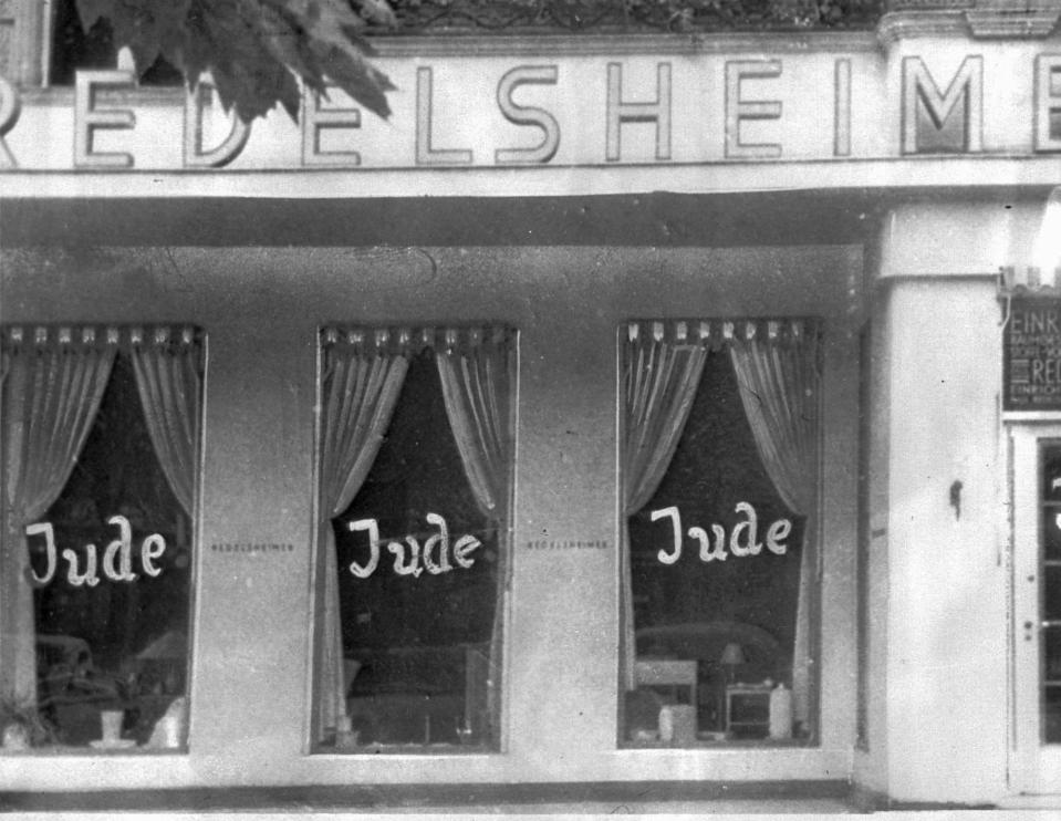 FILE - In this June 19, 1938 file picture, the word Jude (jew) is smeared to the windows of a shop in Berlin run by Jews. On Nov. 9, 1938 Nazi-incited mass riots left more than 91 jews dead, damaged more than 1,000 synagogues and left some 7,500 Jewish businesses ransacked and looted. Before local anti-Jewish laws were enacted, before neighborhood shops and synagogues were destroyed, and before Jews were forced into ghettos, cattle cars, and camps, words were used to stoke the fire of hate. 'ItStartedWithWords' is a digital, Holocaust education campaign posting weekly videos of survivors from across the world reflecting on those moments that led up to the Holocaust. (AP Photo, file)