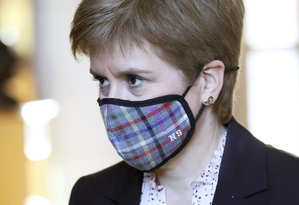 """Scotland's First Minister Nicola Sturgeon wears a mask to protect from coronavirus, in the Scottish Parliament at Holyrood prior to a making a statement outlining further coronavirus restrictions for Scotland, in Edinburgh, Wednesday, Oct. 7, 2020. The Scottish government is banning indoor drinking at bars and forcing restaurants to close in the evening to help contain the coronavirus. First Minister Nicola Sturgeon says the measures were """"a short, sharp action"""" and will last for 16 days starting Friday.  (Andrew Milligan/PA via AP)"""