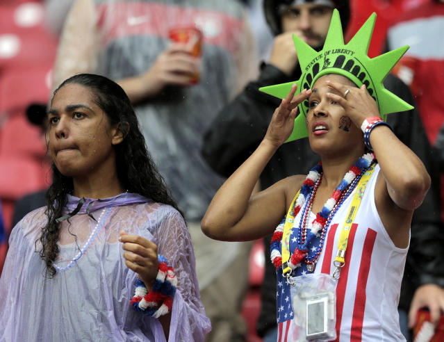 Rain soaked fans wait for the start of the group G World Cup soccer match between the United States and Germany at the Arena Pernambuco in Recife, Brazil, Thursday, June 26, 2014. (AP Photo/Julio Cortez)